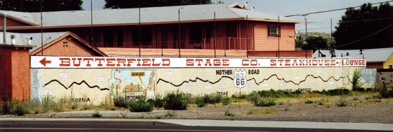 A painted sign directing Route 66ers to the Butterfield Stagecoach Company Steakhouse, a few feet down from the Wigwam Motel, Holbrook, Arizona. July 18, 2001.