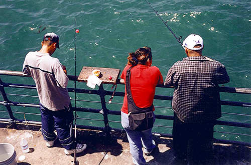 Young Mexican fishermen cast off the Santa Monica Pier to try to catch today's dinner. July 22, 2001.